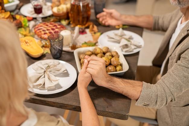 Руки зрелых мужа и жены молятся за праздничным столом с напитками, тарелками с салфетками, печеным картофелем и другой домашней едой
