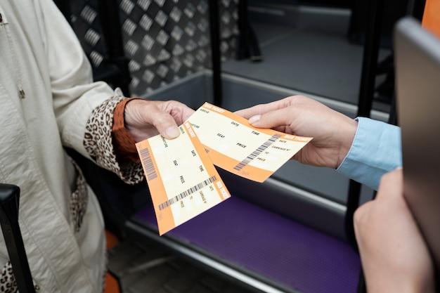 Руки зрелого пассажира и молодого кондуктора автобуса с билетами