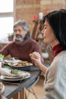 크리스마스 저녁 식사 전에 가정 환경에서 축제 테이블을 제공하여 기도하는 성숙한 여성과 수염 난 남자의 손