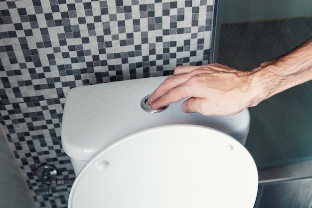 남자의 손, 물 버튼을 누르고, 화장실, 건강 개념을 내리십시오.