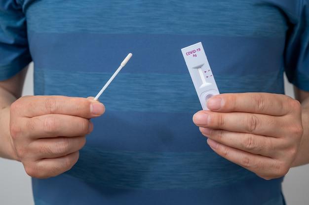Covid-19家庭用抗原キットを使用してコロナウイルスを検査する男性の手。