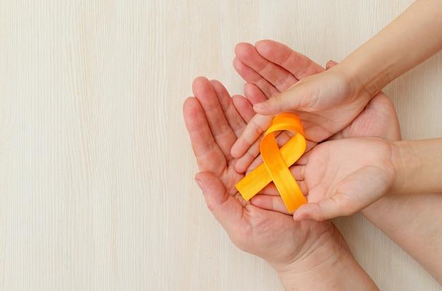 Руки матери и ребенка держат оранжевую ленту на белом фоне всемирный день борьбы с рассеянным склерозом