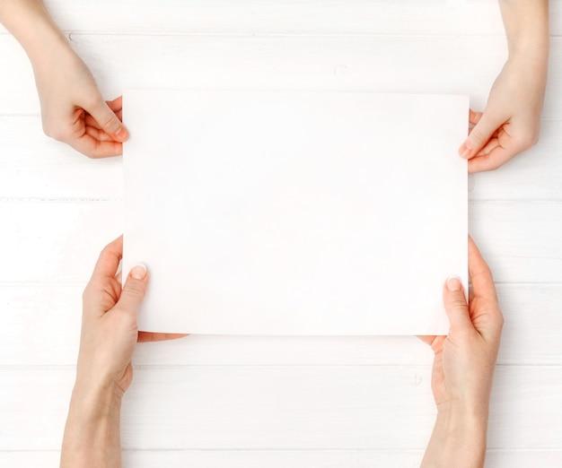 デザイン用のサイズの空白の白い紙を持つ母と娘の手