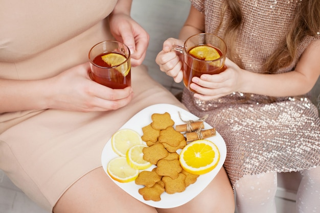 お祝いのクリスマスにレモンとホットtシャツのカップを保持している母と少女の手