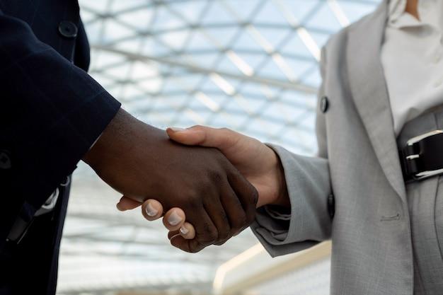 握手中の多民族パートナーの手