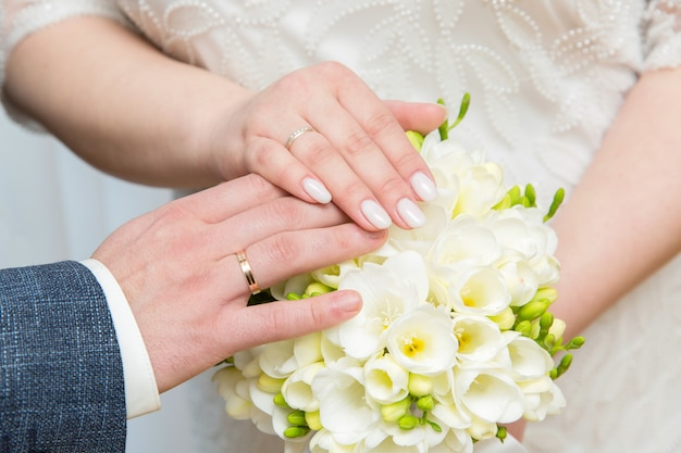 Руки молодоженов в обручальных кольцах на фоне свадебного букета