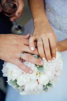 Руки молодоженов с обручальными кольцами - жених и невеста на свадебной церемонии.
