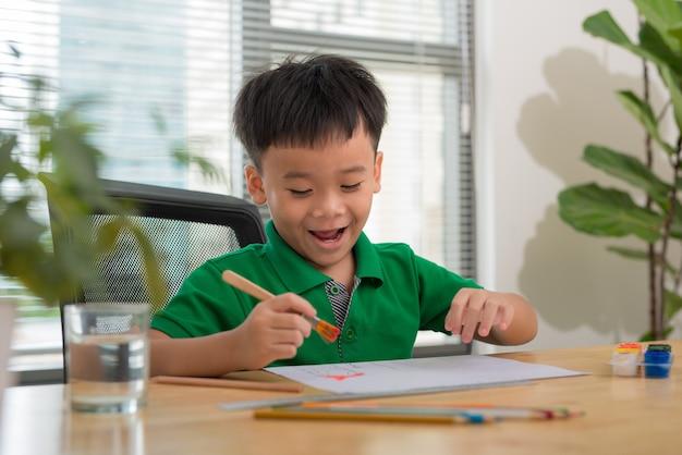 Руки рисования маленького мальчика и стол для творчества