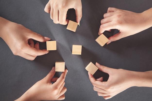 木製の立方体を見せている人々の手。