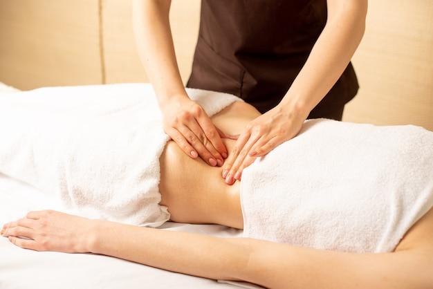 痛みに苦しむ患者の腹部触診を行う医師の手