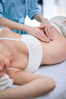Руки физиотерапевта и остеопата делают профессиональный массаж будущей маме