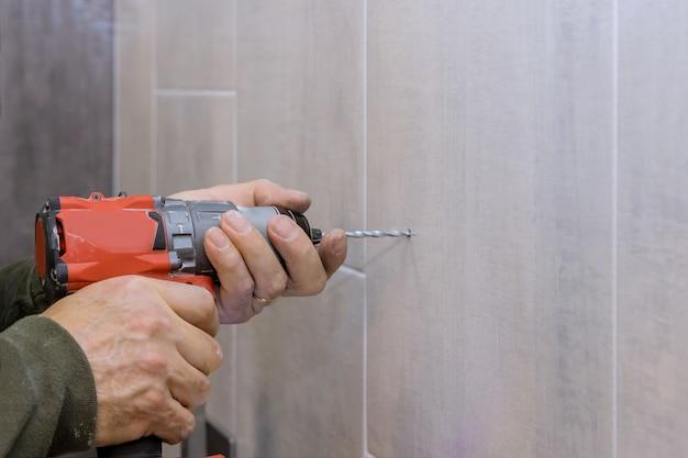 드릴을 사용하여 욕실 설치를 위해 타일 욕실 벽에 새 구멍을 만드는 배관공의 손