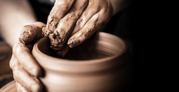 검은 배경에 진흙 냄비를 만드는 도공의 손