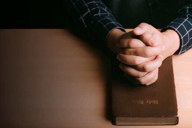 木製の机の背景に若い男と聖書を祈る手。人は手を取り合って、神、聖書の祝福を祈り求めます。