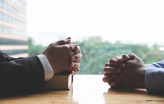 Руки молящегося молодого человека и библии