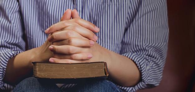 Руки молиться молодой женщины и библии на деревянном фоне стола. женщина соединяются руки, чтобы молиться и искать благословения бога, библии. фон баннера