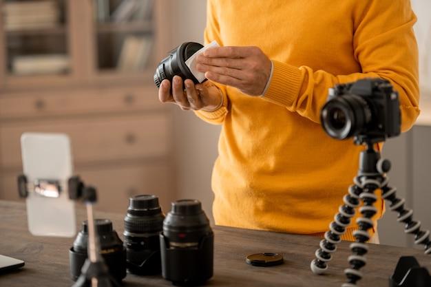 온라인 청중을위한 수업을 만드는 동안 스마트 폰 앞 삼각대에 포토 카메라를 고정하는 전문 스톡 사진 작가의 손
