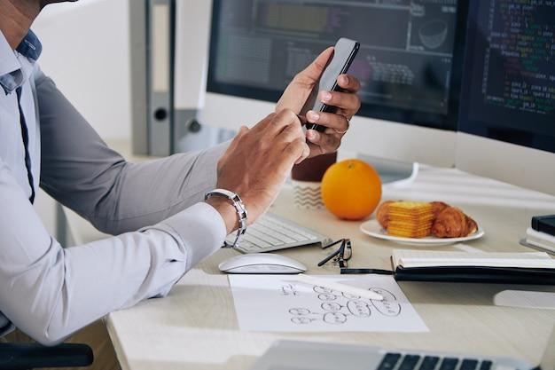 オフィスデスクで新しいプロジェクトに取り組んでいるときにクライアントからのテキストメッセージをチェックするプログラマーの手