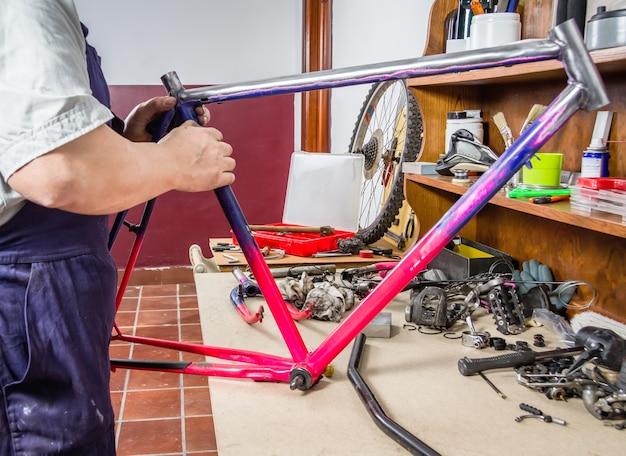 ワークショップで破損したフレームバイクを掃除する実際の自転車整備士の手