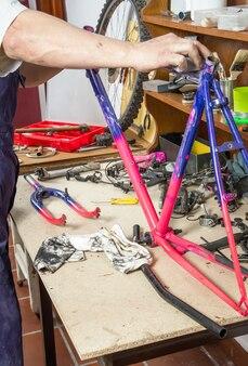 本物の自転車整備士のサンディングフレームバイクの手