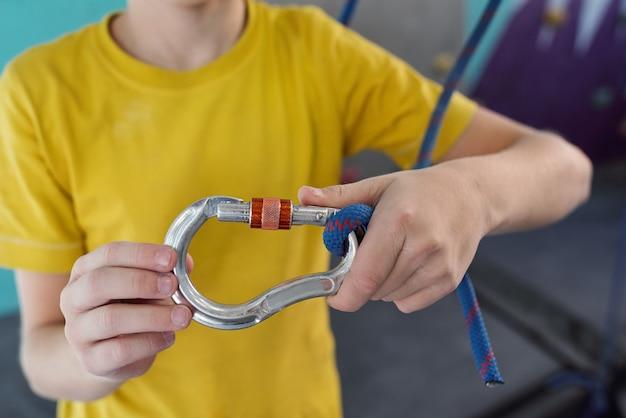 ジムでトレーニングをするつもりの間にロープでクライミングカラビナを保持している黄色のtシャツの男子生徒の手