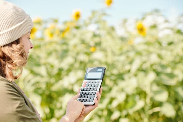 디스플레이에 계산기를 들고 녹색 식물과 잎에 대해 이 숫자가 있는 버튼을 누르는 수석 남성 농부의 손