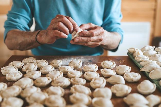 台所のテーブルの上で肉を使って小さな自家製の生餃子を調理して成形する年配の男性の手。国の伝統的なロシア料理。