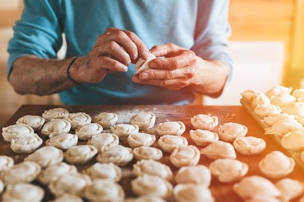 台所のテーブルの上で肉を使って小さな自家製の生餃子を調理して成形する年配の男性の手