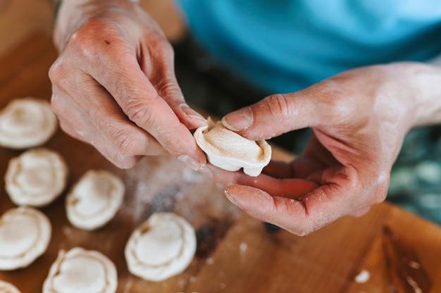 台所のテーブルの上で肉を使って小さな自家製の生餃子を調理して成形する年配の男性の手。