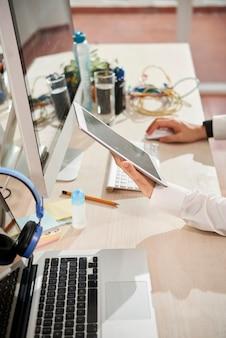 デジタルタブレットでレポートや電子メールを読んだり、オフィスのデスクでコンピューターを操作したりするソフトウェアエンジニアの手