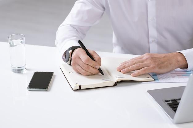 Руки успешного работодателя с ручкой над страницей записной книжки, записывающей план на день, сидя за столом