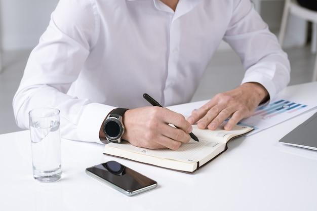 机のそばに座って作業メモやその日の計画を立てる白いシャツを着た成功した男性起業家の手