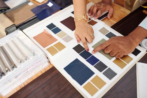 オーダーメイドのスーツを作るためにカタログから生地を選ぶ仕立て屋とクライアントの手