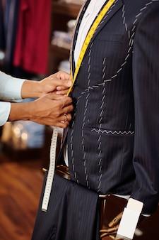 彼のアトリエで働くときの巻尺でテーラー測定ジャケット襟の手