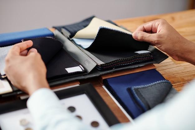 オーダーメイドのスーツを作るために選択する2種類の黒いウール生地に触れる仕立て屋の手