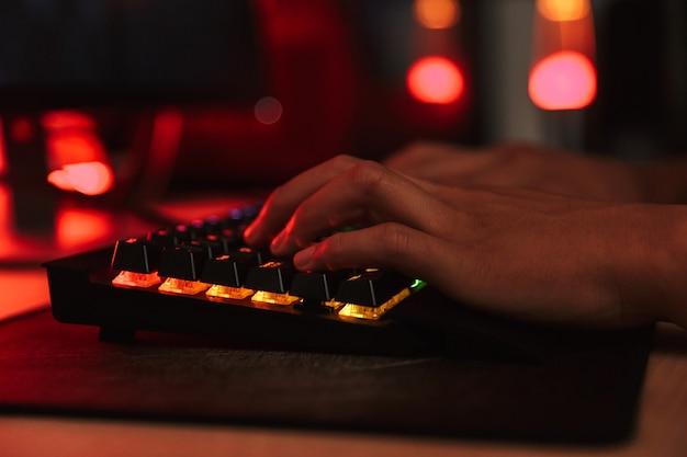 Руки мальчика-подростка-геймера, играющего в видеоигры на компьютере в темной комнате, используя красочную клавиатуру с подсветкой