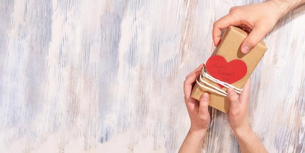Руки девочки-подростка дарят папе подарок ко дню отца с открыткой в форме сердца
