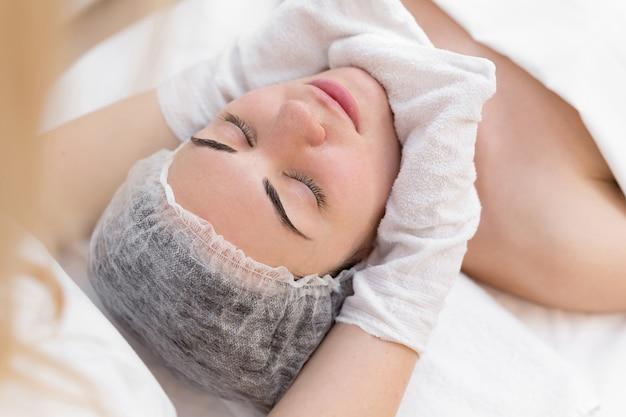 美容師の手が美容センターの女の子の顔を白い手袋で拭きます。