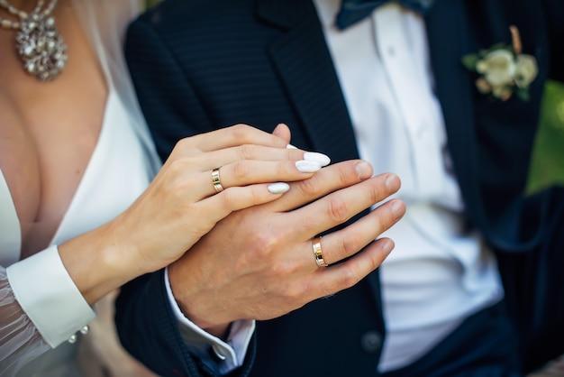 Руки жениха и невесты крупным планом. золотые обручальные кольца на пальцах молодоженов. понятие о браке.