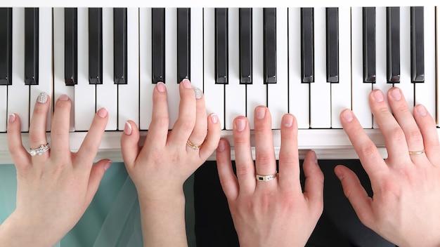 피아노를 치는 신랑 신부의 손. 새 가족 연합의 공동 행동
