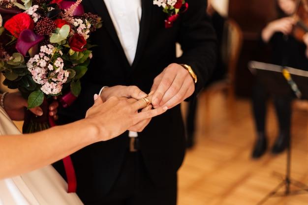 花束のクローズアップと新郎新婦の手