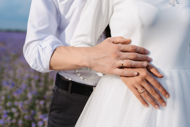 Руки жениха и невесты с золотыми обручальными кольцами на фоне белого платья