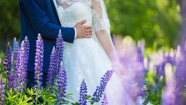 Руки жениха и невесты с кольцами на красивый свадебный букет