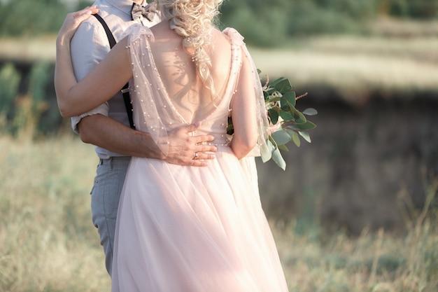 花のウェディングブーケと新郎新婦の手。ファインアート写真。