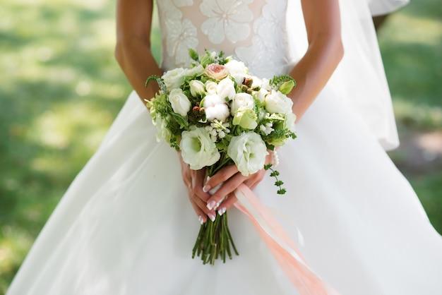 Руки невесты и букет невесты.