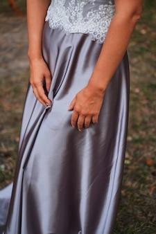 花嫁の手は、シルクバイオレットのドレスの上にあります。結婚式の前に待っています