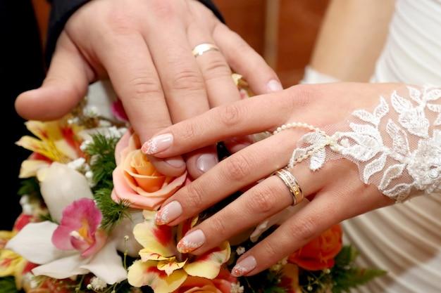 웨딩 부케의 배경에 신랑과 신부의 손. 사랑과 가족 관계