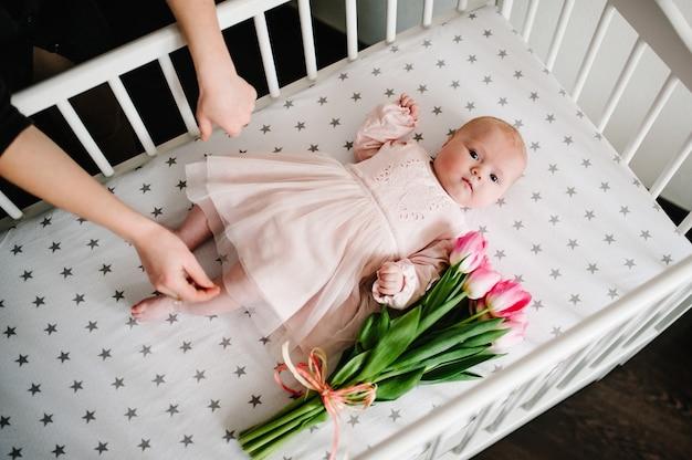 休日に贈り物をする母の手。ベッドの上のピンクの花チューリップの花束と生まれたばかりの赤ちゃん女の子。母の日。