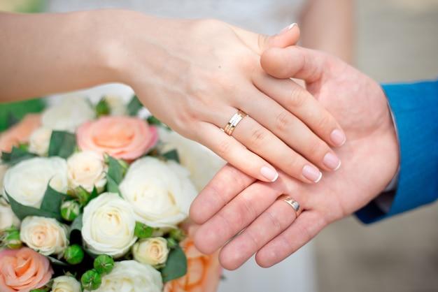バラのウェディングブーケのテーブルにゴールドの結婚指輪のクローズアップと新郎新婦の手