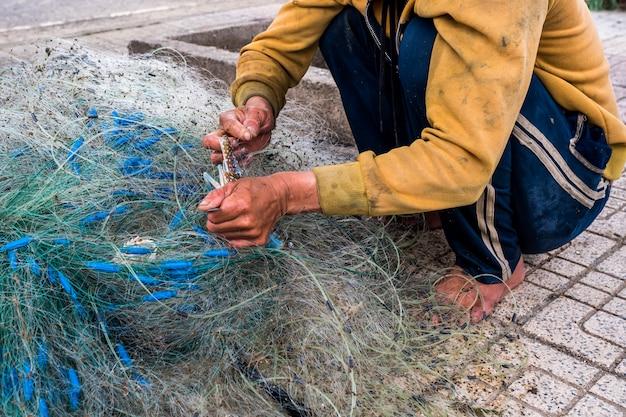 Руки старого рыбака распутывают рыболовные сети, нячанг